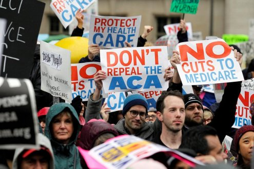 Demonstrators hold signs in support of the Affordable Care Act at a gathering before the start of a protest march near the hotel where House and Senate Republicans are attending a retreat, in Philadelphia